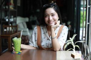 mulheres asiáticas sorrindo e felizes relaxando e segurando uma xícara de chá em uma cafeteria foto