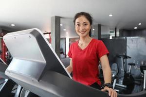 mulheres asiáticas correndo tênis esportivos na academia enquanto uma jovem mulher caucasiana está correndo na esteira foto