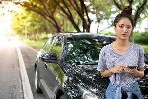 Mulher asiática usando telefone celular enquanto olha e homem estressado sentado após uma quebra de carro na rua foto