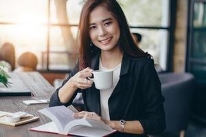 Mulher de negócios asiática está trabalhando e tomando café na hora de relaxar foto