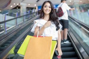 Mulher asiática e linda garota estão segurando sacolas de compras, usando um telefone inteligente e sorrindo enquanto fazem compras no supermercado foto