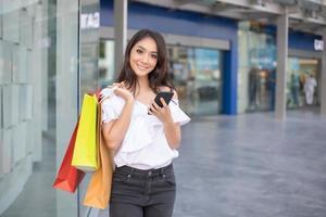 Mulher asiática e linda garota segurando sacolas de compras sorrindo enquanto fazem compras no supermercado foto