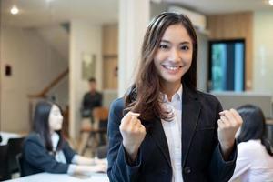 Sucesso e conceito vencedor de mulheres de negócios asiáticas - equipe feliz com as mãos levantadas celebrando o avanço e as conquistas foto