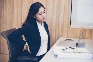 empresários asiáticos que trabalham duro até sentirem dores nas costas. foto