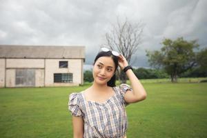 em pé mulher segurando e sorrindo feliz no parque. foto