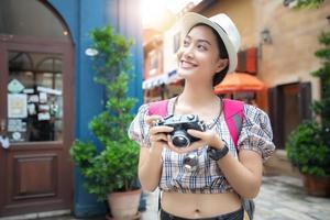 mulheres asiáticas usam camisa xadrez e mochilas caminhando juntas e felizes estão tirando fotos e selfie, relaxando na viagem do conceito de férias