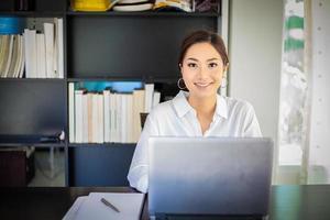 Mulheres de negócios asiáticas usando notebook e sorrindo felizes por trabalhar foto