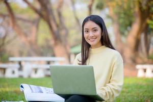 estudantes universitários de mulheres asiáticas sorrindo e sentados na grama verde trabalhando e lendo juntos em um parque. foto