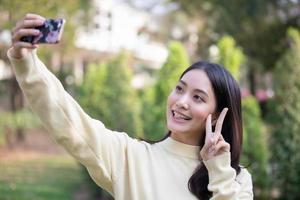 mulheres asiáticas sorrindo tirando fotos e tirando selfie