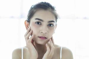 mulheres asiáticas lindas com pele limpa, fresca, tocam o próprio rosto. tratamento facial. cosmetologia, beleza e spa foto