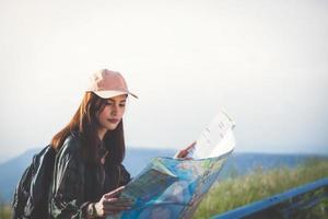 mulheres jovens asiáticas caminhando com mochilas de amigos caminhando juntos e olhando o mapa e tirando a câmera fotográfica na estrada e parecendo feliz, relaxe o tempo na viagem do conceito de férias foto
