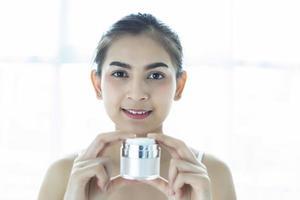 uma linda mulher asiática usando um produto para a pele, hidratante ou loção para cuidar de sua pele seca. creme hidratante nas mãos femininas. foto