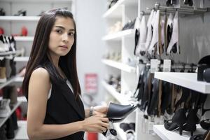 Mulher jovem sorridente asiática com compras e compra no mercado de supermercado de shopping foto