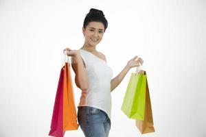 Linda garota asiática segurando sacolas de compras e sorrindo foto