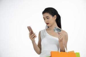 Mulher asiática e linda garota estão segurando sacolas de compras, usando um telefone inteligente e sorrindo enquanto fazem compras e compram com cartão de crédito foto