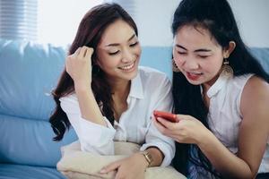 jovem olhando para o telefone da amiga e se sentindo animada e sorridente enquanto está sentada na sala de estar de casa foto