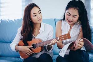 duas mulheres asiáticas se divertindo tocando cavaquinho e sorrindo em casa para relaxar foto