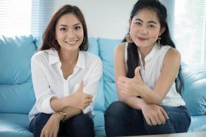 duas mulheres amigas competitivas animadas, alegres, alegres e sorridentes, jovem atraente sinal de positivo no sofá na sala de estar foto