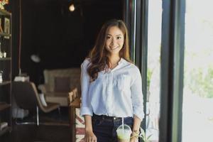 mulheres asiáticas em pé sorrindo e relaxando feliz em um café depois de trabalhar em um escritório de sucesso. foto