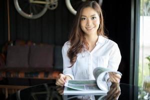 mulheres asiáticas sorrindo e lendo um livro para relaxar no café foto