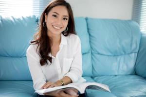 mulheres asiáticas sorrindo e lendo um livro para relaxar em casa foto