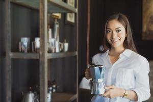 menina asiática em pé segurando um sorriso de cafeteira e divirta-se relaxando em uma cafeteria depois de trabalhar em um escritório de sucesso. foto
