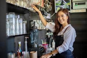 Barista de mulheres asiáticas sorrindo e usando a máquina de café no balcão da cafeteria - conceito de café de comida e bebida de proprietário de uma pequena empresa de trabalho mulher foto