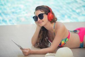 as mulheres usam biquínis, leem livros e ouvem música na piscina recreativa de verão. foto