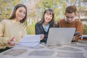 os alunos do grupo sorriem e se divertem também ajuda a compartilhar ideias no trabalho e no projeto. e também revise o livro antes do exame no jardim. foto
