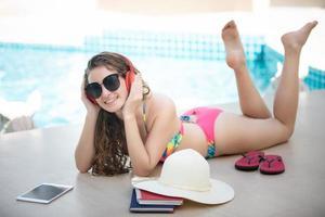 as mulheres usam biquínis, ela lê livros e ouve música na piscina recreativa de verão. foto