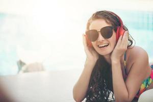 mulheres felizes usam biquínis, leem livros e ouvem música na piscina recreativa de verão foto