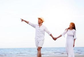 Amante de casais românticos felizes de mãos dadas caminhando na praia foto