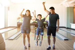 família se divertindo no clube de boliche depois de jogar bola de boliche com foco suave e embaçado foto