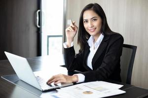 mulheres de negócios asiáticas segurando uma caneta e documentos de análise na mesa do escritório com um computador laptop e um diagrama financeiro gráfico trabalhando em segundo plano foto