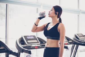mulher desportiva Ásia bebendo água após exercícios no ginásio. fitness - conceito de saudável foto