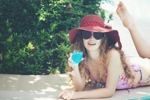 as mulheres usam biquínis e bebem coquetéis no verão quente na piscina. foto