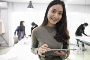 Alunos de mulheres asiáticas sorriem e se divertem e usando o tablet também ajuda a compartilhar ideias no trabalho e no projeto. foto