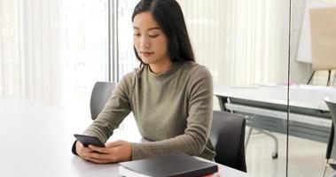 Alunos de mulheres asiáticas sorriem e se divertem e usando smartphone e tablet também ajuda a compartilhar ideias no trabalho e no projeto. foto