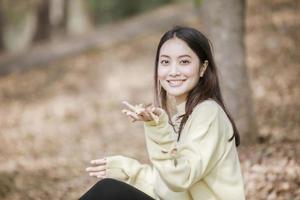 linda mulher asiática sorrindo, garota feliz e vestindo roupas quentes, inverno e outono retrato ao ar livre no parque foto