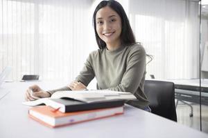 Alunos de mulheres asiáticas sorriem e lendo o livro e usando o caderno para ajuda a compartilhar ideias no trabalho e no projeto. e também revisar o livro antes do exame foto
