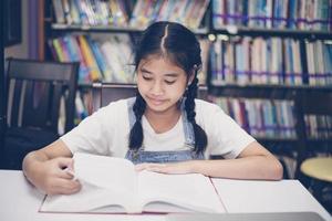 estudantes asiáticos lendo livros na biblioteca. foto