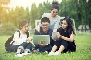 grupo asiático de alunos compartilhando ideias para trabalhar no jardim do gramado do campus foto