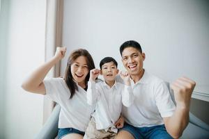família animada e feliz com os braços levantados enquanto assiste televisão em casa foto