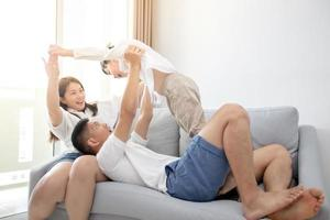família asiática feliz com o filho em casa no sofá brincando e rindo foto