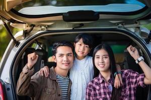 menina feliz com uma família asiática sentada no carro para aproveitar a viagem e as férias de verão em uma van de camping foto