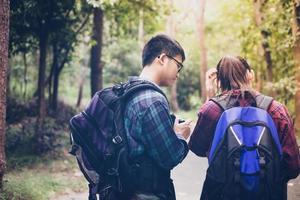 Grupo asiático de jovens caminhando com mochilas de amigos caminhando juntos e olhando o mapa e tirando a câmera fotográfica na estrada e parecendo feliz, relaxe o tempo na viagem do conceito de férias foto