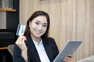 mulher asiática usando tablet e fazendo compras online com cartão de crédito foto