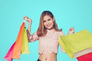Mulher asiática e linda garota segurando sacolas de compras sorrindo enquanto fazem compras foto
