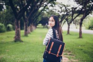 bela aluna asiática segurando livros e sorrindo para a câmera e o conceito de aprendizagem e educação no parque no verão para relaxar ao pôr do sol com uma luz quente foto