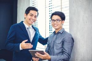 Empresários asiáticos e grupo usando notebook para parceiros de negócios discutindo documentos e ideias em reuniões e mulheres de negócios sorrindo felizes por trabalhar foto
